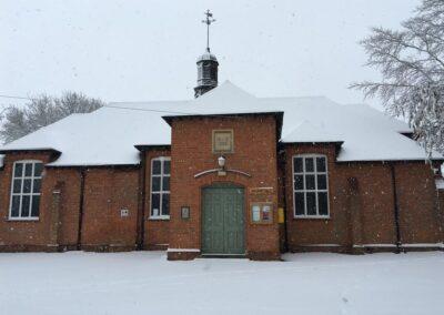 Exterior of Dumbleton Village Hall in winter snow